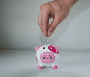 man placing coin in piggy bank