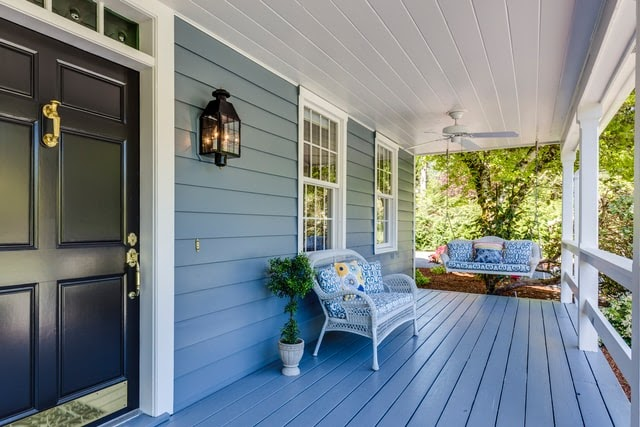 front of the house with blue color porch and white couch