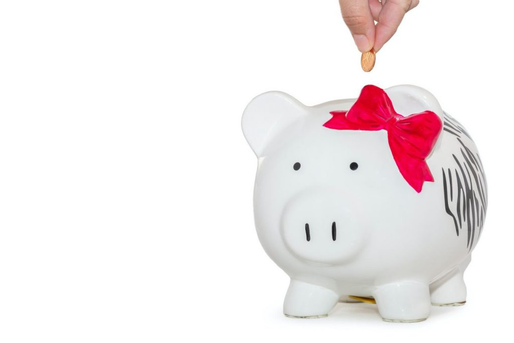 putting a penny in a white piggy bank